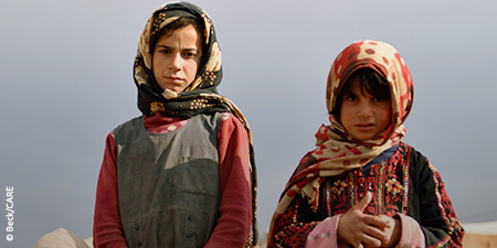 Two refugee girls in colorful headscarves look at the camera with serious expressions