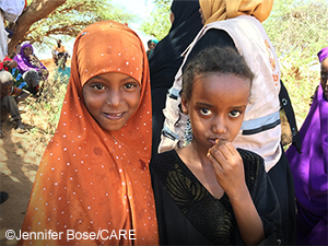 Two refugee girls look at the camera with serious expressions