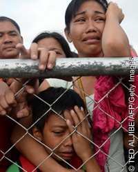 A mother and her child cry as they beg authorities for seats on flights by military C-130 planes out at the airport in Tacloban, Leyte province, central Philippines