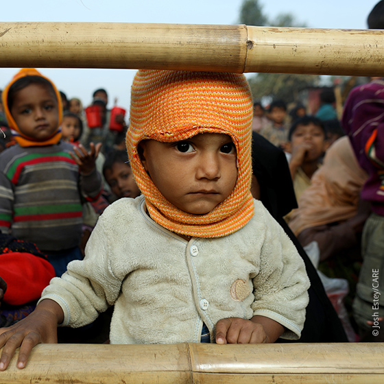Refugee toddler surrounded by other refugees