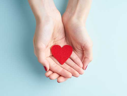 Two hands cupped around a red paper heart