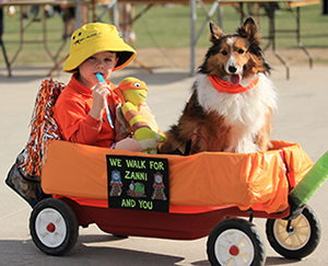 child in a wagon with a dog