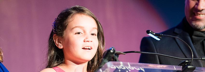 Nayeli speaking at podium