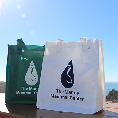 green shopping bag and white shopping bag with Marine Mammal Center logo