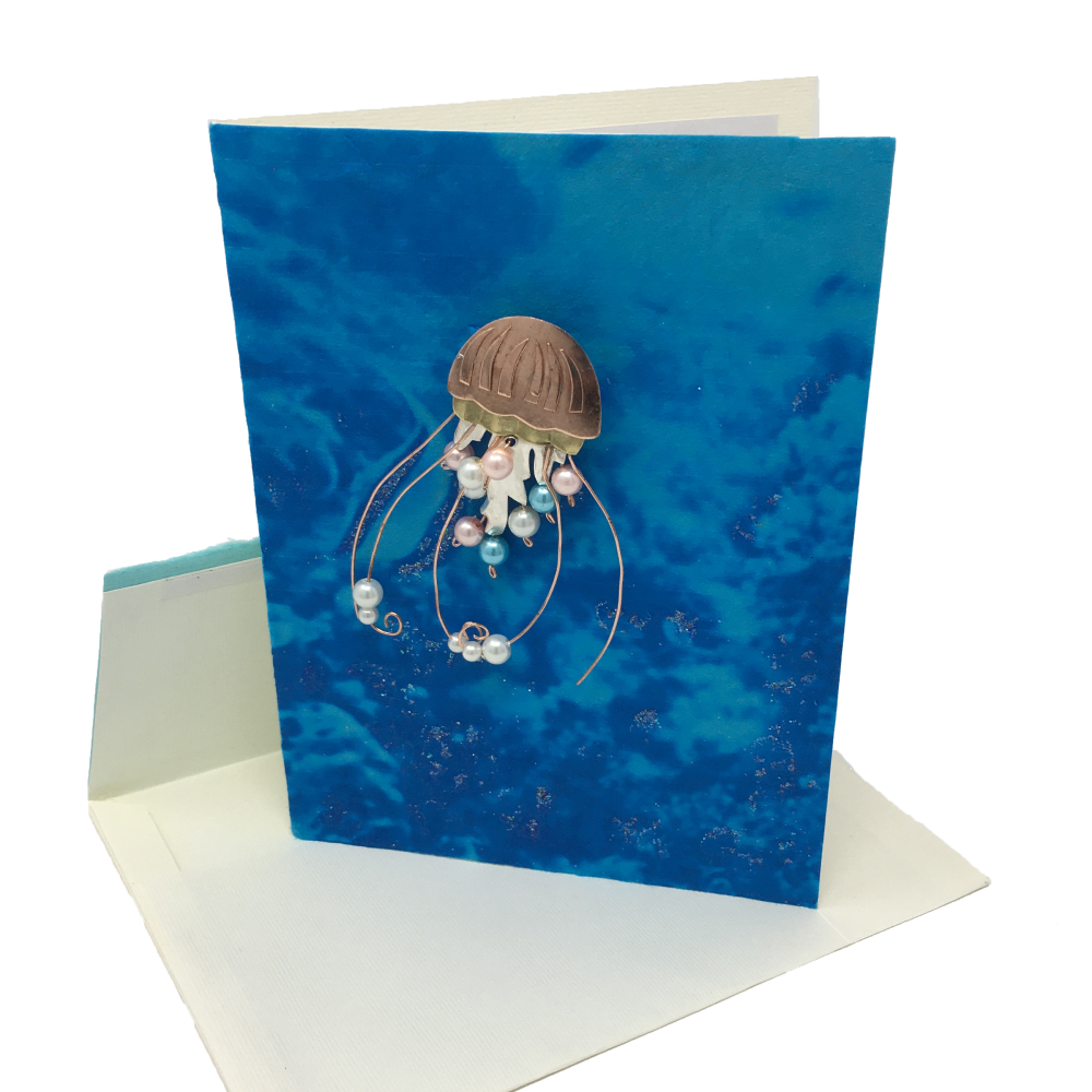 blue and tan greeting card with metal sea jelly pin attached
