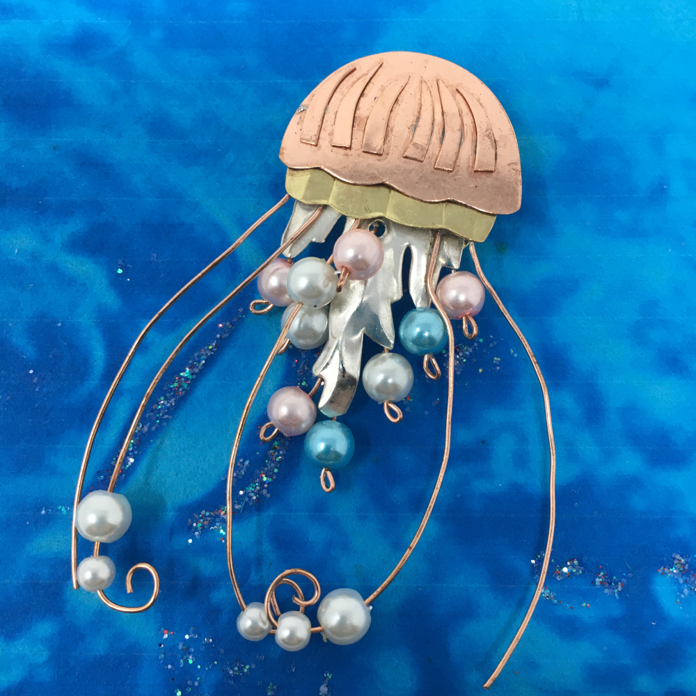 copper-colored metal sea jelly pin with white, pink, and blue beads