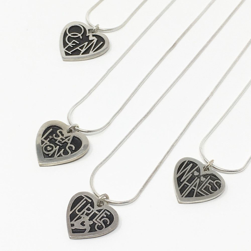 sterling silver heart-shaped pendants with ocean-themed lettering