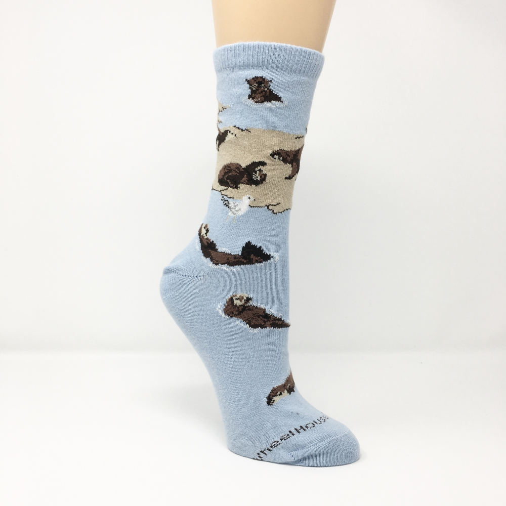 light blue socks featuring numerous sea otters on land and in water